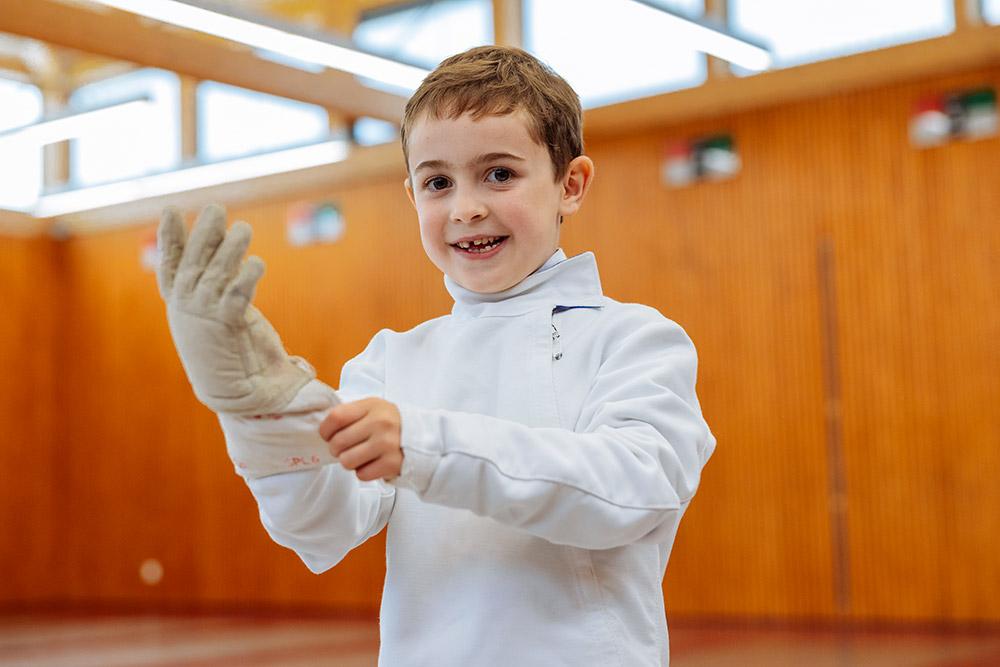 petit escrimeur souriant enfilant son gant